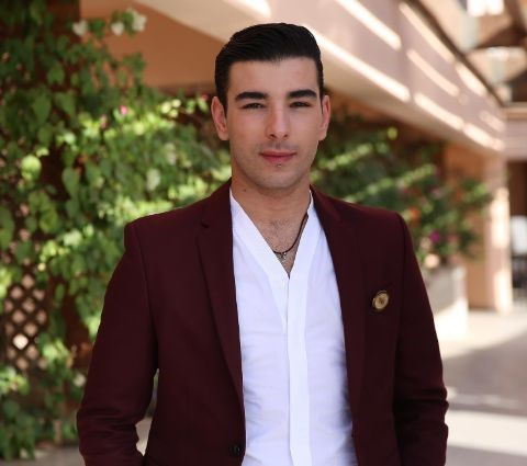 Fares Landoulsi wearing white shirt and red blazer.